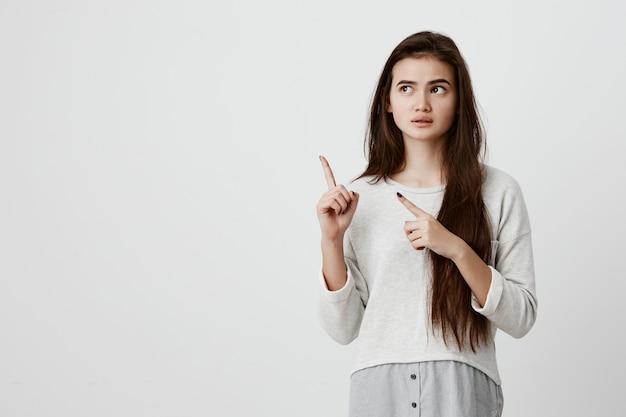 Удивленная молодая женская модель с прямыми длинными темными волосами, одетая в повседневную одежду, смотрящая в сторону, указывающая указательными пальцами на место для копирования