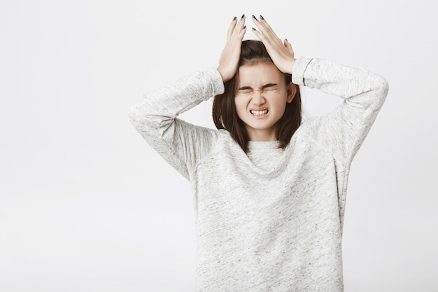 Портрет милой европейской женщины, которая страдает от головной боли, держа руки на имел и сжимает зубы.