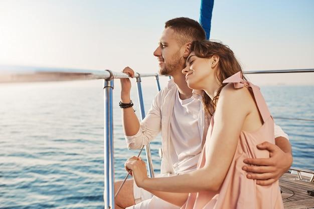 プライベートヨットの船首に座って海の景色を楽しみながら抱いて愛のスタイリッシュなカップルの肖像画。夫は新婚旅行を祝って、彼の妻を美しい暖かい国に連れて行きました