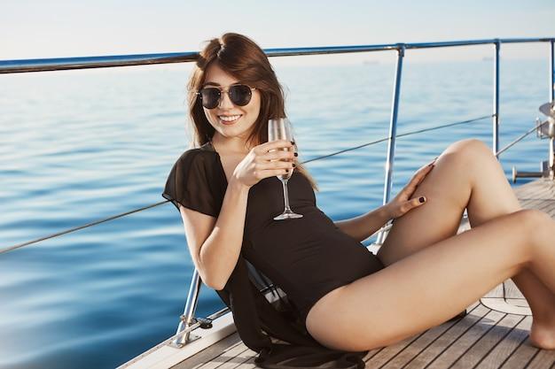 黒の水着でヨットの床に座っている間シャンパンをすすりながらメガネで魅力的なヨーロッパのブルネット。ボートに乗って余暇を過ごす金持ちの女