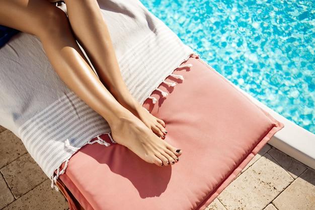 スイミングプールのそばの長椅子に横たわる女