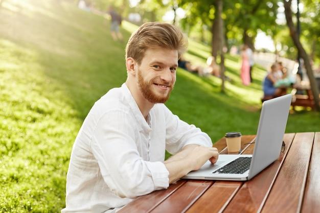 公園でラップトップコンピューターを持つ成熟した生姜ハンサムな男