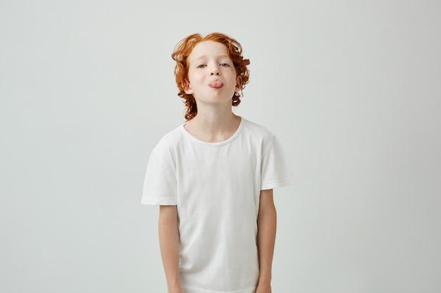 Крупным планом портрет красивый рыжий малыш в белой футболке, показывая язык