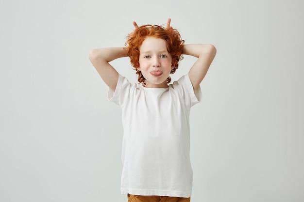 室内で楽しんで、彼女の舌を突き出し、指で角を作るそばかすのある面白い赤毛の小さな男の子の肖像画。