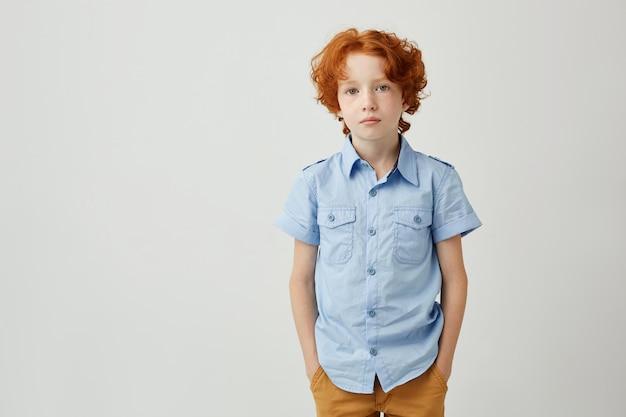 生姜髪とそばかすのポケットに手を繋いでいる美しい小さな男の子