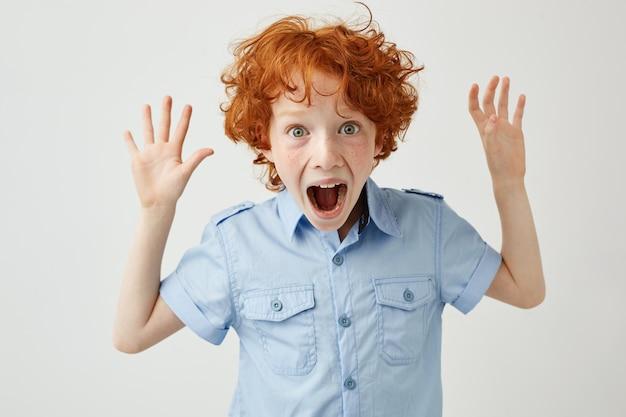 生姜髪とそばかすが手を広げて、大声で叫んでいるかわいい男の子のクローズアップ