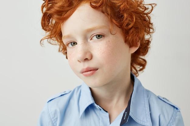 そばかすと真面目な表情で見ている大きな灰色の目で陽気な赤毛の子供の肖像画を間近します。