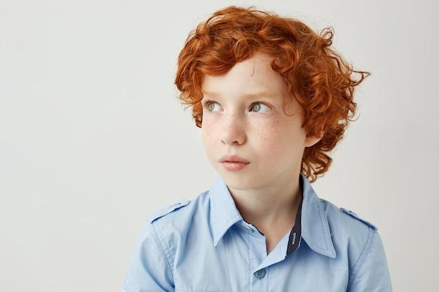 赤い巻き毛とそばかすのある見栄えの良い小さな男の子のクローズアップ。コピースペース
