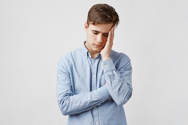 青のカジュアルシャツで疲れきった若い男の写真。