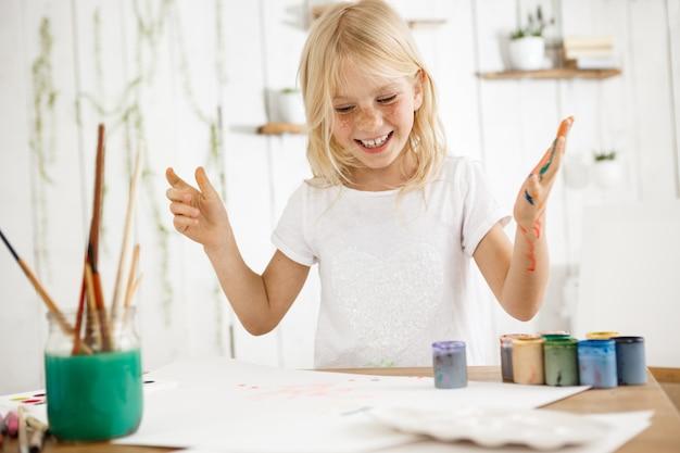 笑顔で、幸せで陽気なブロンドの女の子が彼女の歯を見せて、絵を描きながら楽しんでいます。女性のそばかすのある子供は、さまざまな色の塗料で彼女の手を台無しにしました。