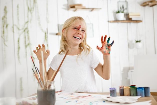 Усмехаясь с зубами милая маленькая блондинка показывая ее руки в краске. веселая семилетняя девочка занята беспорядочным рисованием краски.