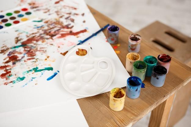 Обрезанный снимок деревянного стола с краской, кистями, палитрой и рисунками, сделанными детьми