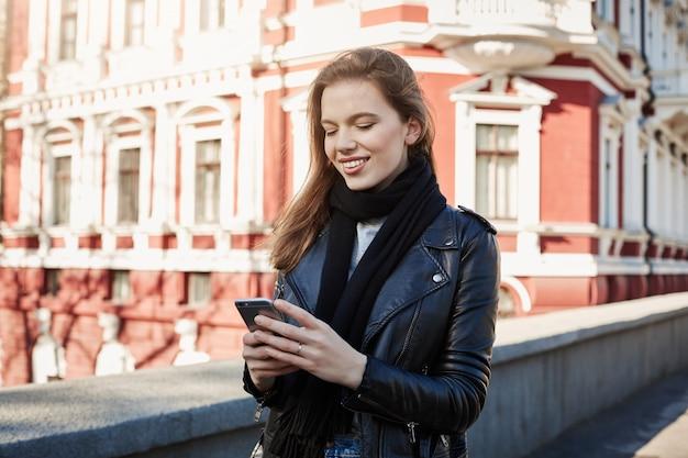 大都会での生活。通りに立って、スマートフォンとテキストメッセージを保持している魅力的なスタイリッシュな女性の肖像画