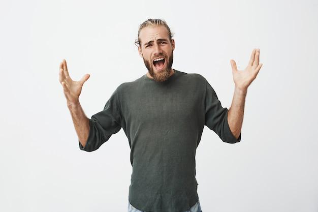 スタイリッシュな髪型が手を広げて乱暴に叫んでいる動揺の成熟したひげを生やした男