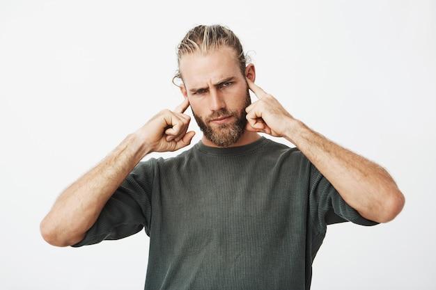 彼の耳をカバーする魅力的な深刻なひげを生やした男