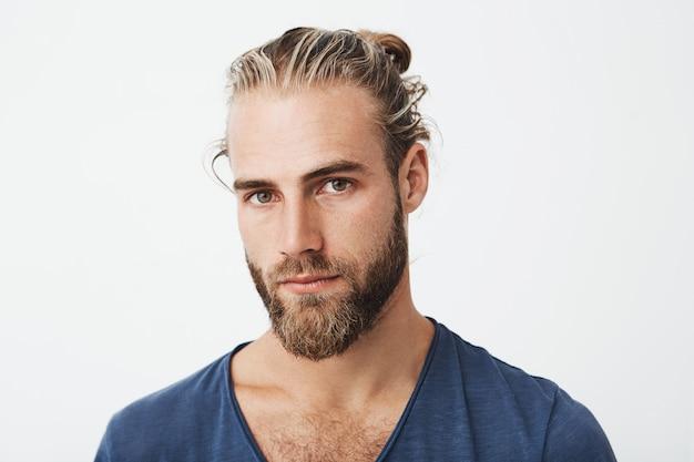 Портрет симпатичного нордического небритого мужчины с модной прической, позирующей