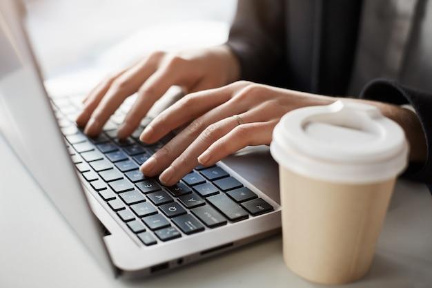 Женщина крупного плана работая в компьтер-книжке пока сидящ в офисе