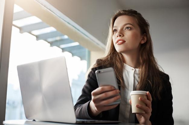 魅力的な女性会社員、ノートパソコンと一緒にカフェに座って、コーヒーを飲みながらスマートフォンを持って、よそ見しながら夢を見る