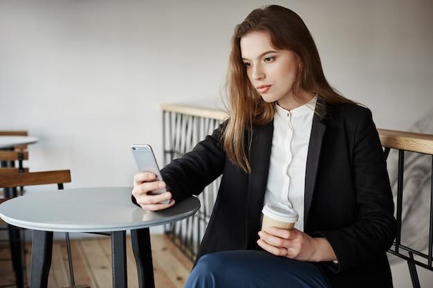 スマートフォンでカフェで魅力的な若い女性