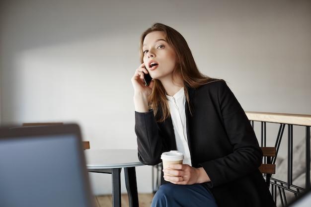 Красивая молодая деловая женщина в кафе разговаривает по телефону