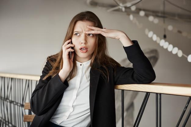 電話で話しているカフェで心配している若い実業家