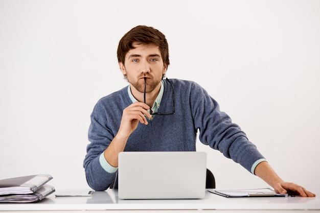 Сконцентрированный бизнесмен сидя на столе офиса используя компьтер-книжку смотря