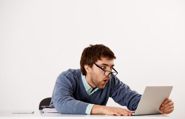 ショックを受けてびっくりして感銘を受けたサラリーマン、男性起業家が机に座って、ノートパソコンの画面を見つめず、大きなニュースを読んでいる