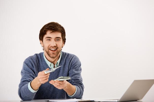 Молодой улыбающийся бизнесмен дает наличные деньги, сидит за столом с ноутбуком, считает деньги, дает половину дохода деловому партнеру