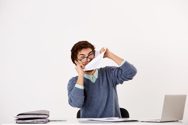 憤慨しているビジネスマンは紙を引き裂き、怒って文書を噛んで、オフィスの机に座って感情的に燃え尽きています