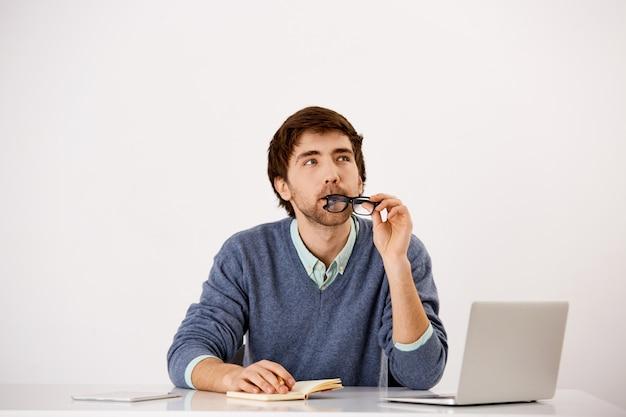 思いやりのあるビジネスマンがオフィスの机に座って、メガネの縁を噛んで、考えを調べ、ノートに書いてインスピレーションを検索