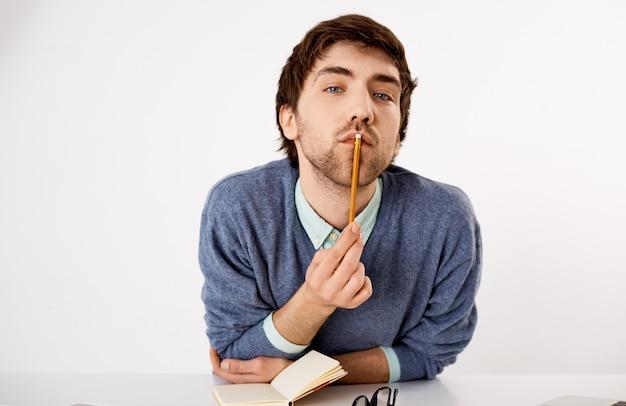 思いやりのあるハンサムな男性の雇用主のクローズアップの肖像画、テーブルに寄りかかって、鉛筆を使って考えているように唇に触れ、新しいコンテンツを作成し、考えを書き留めている