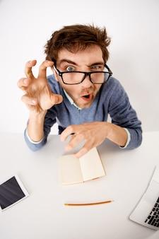 面白い顔をゆがめる男性従業員、オフィスワーカーが仕事でだまして、手でモンスターの爪を作り、凝視