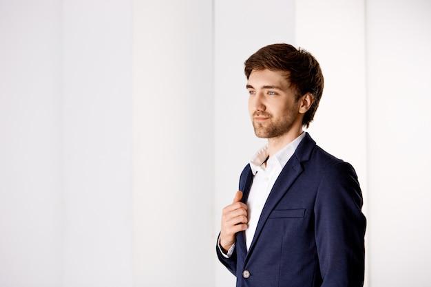 ビジネス、成功、人々の概念。スーツ、スタンドオフィスでハンサムなスタイリッシュなビジネスマン、窓からの眺めを楽しみ、満足している笑顔