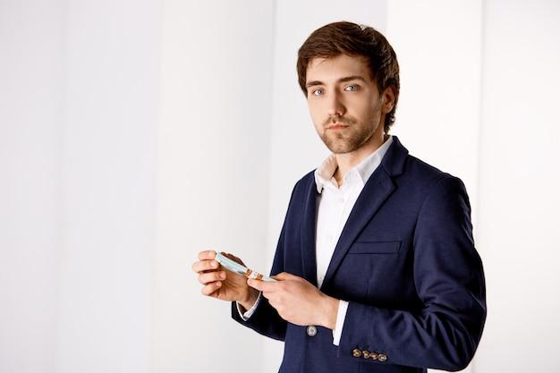 Бизнес, финансы и концепция дохода. красивый богатый мужчина предприниматель стоит в офисе, носит костюм, считает деньги, держит наличные и выглядит серьезно