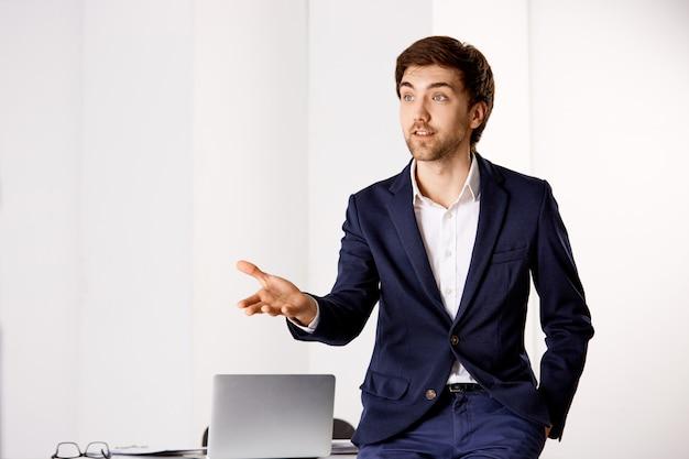 思慮深く、スマートで創造的なビジネスマンは、同僚と話しながらテーブルに寄りかかり、頭を身振りで示す、ビジネス会議を行う