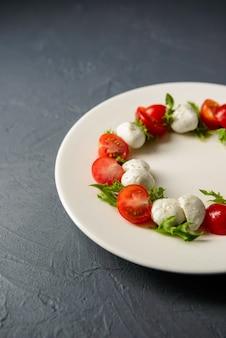 高価なレストラン、健康食品のコンセプトで提供されるカプレーゼサラダの写真をトリミング
