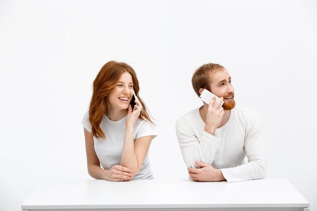 赤毛の男性と女性がテーブルで電話で話しています。