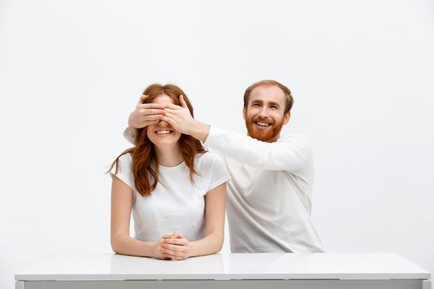幸せな男は女性の目を覆い、驚きを作る
