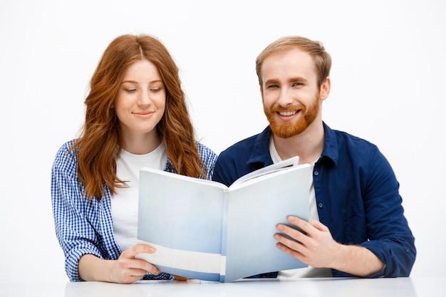 Счастливые взрослые рыжие братья и сестры смотрят старый фотоальбом