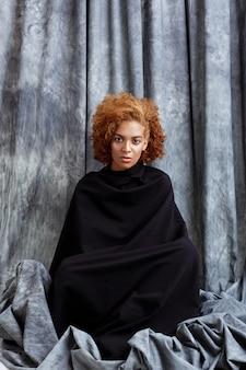若い美しい女性がポーズ、灰色の布で包む