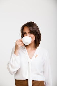コーヒーを飲み、笑みを浮かべて成功した女性の上司