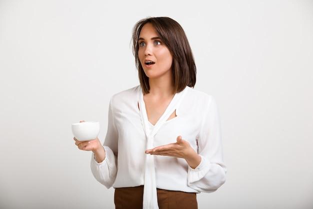 コーヒーを飲み、同僚に話している成功した女性の上司