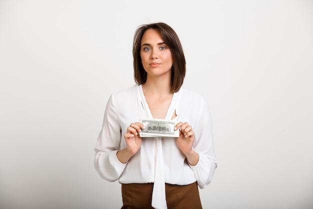 Успешная богатая модная женщина показывает деньги