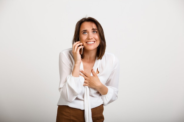 電話を話して幸せなエレガントな女性