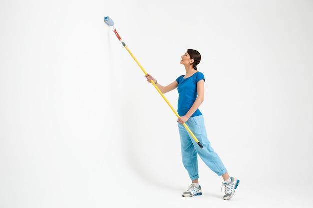 Молодая женщина красит стену, делает ремонтные работы