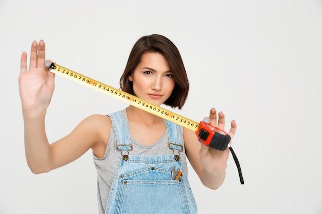 巻尺でかわいい女性は家を改装します