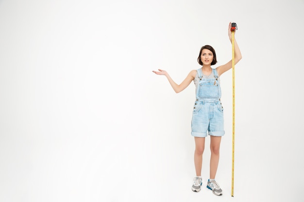 女性の完全な長さの肖像画はテープで自分を測定します。