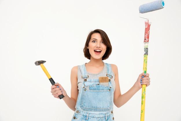 Женщина держит молоток и малярную кисть, ремонтирует дом