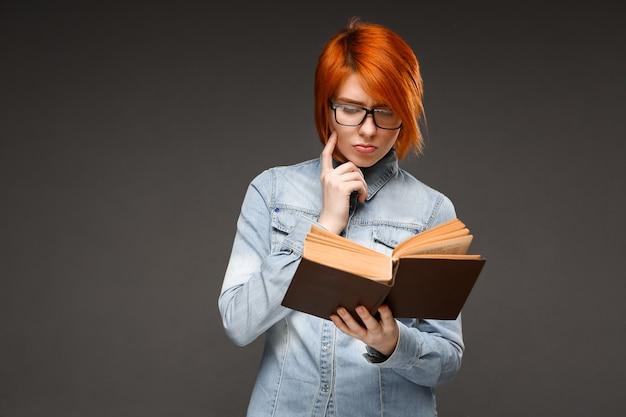 Рыжая студентка читает книгу, изучает
