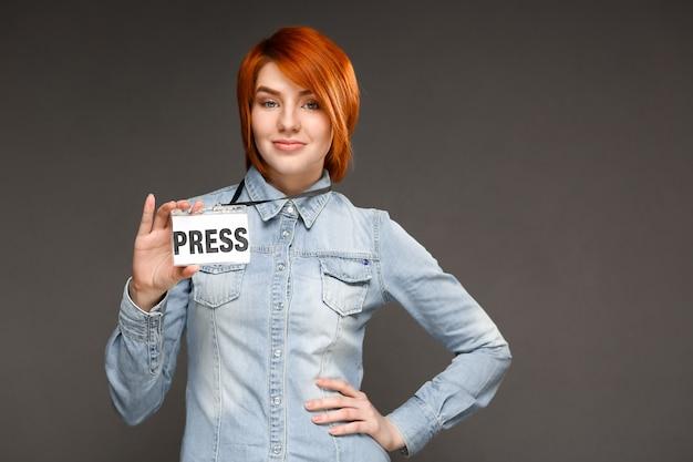 赤毛自信のジャーナリストは彼女の記者バッジを表示します